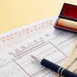 相続税の申告書と印鑑とお札とボールペンの写真