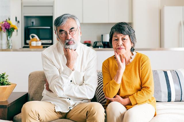 老夫婦がソファーに座って腕を組んで悩んでいる写真