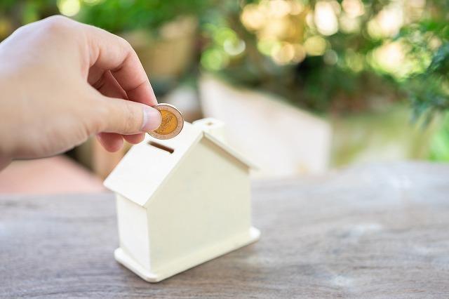 家の形をした貯金箱にコインを入れようとしている写真