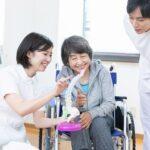 車いすのお婆さんに骨の模型で説明する若い女性の療法士