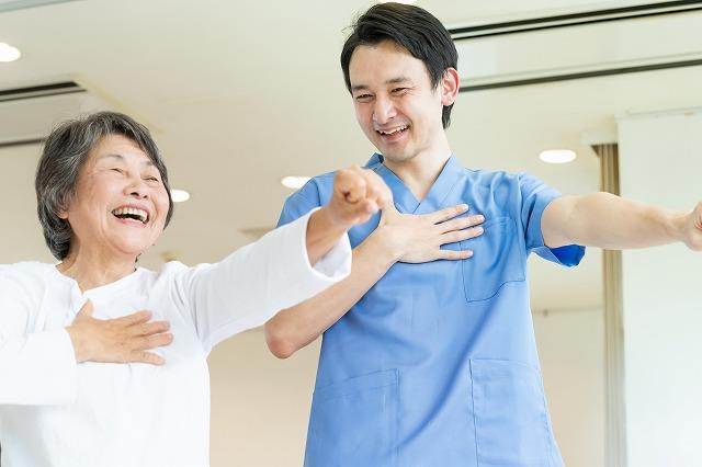 笑顔のお婆さんとリハビリする若い男性の療法士