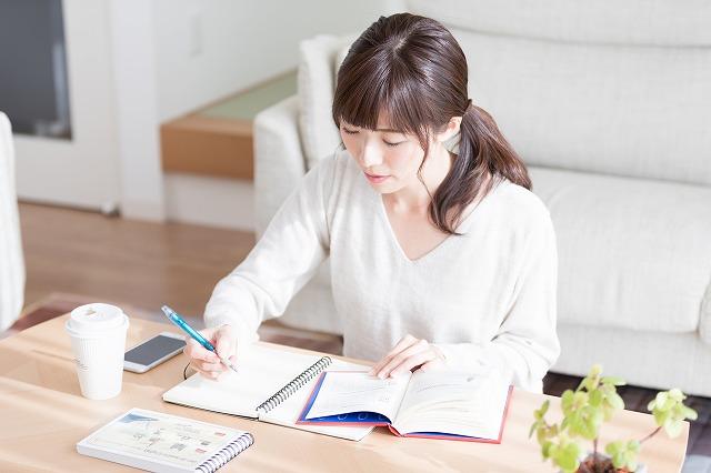 女性が机で勉強している
