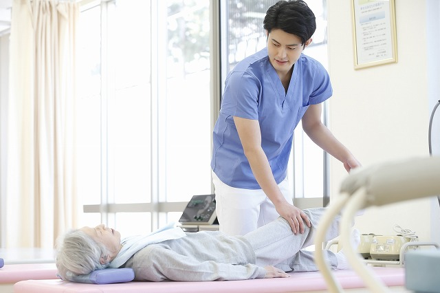 寝ているお婆さんの足を持ってリハビリする若い男性の療法士