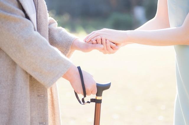 杖を持った人と手をつないでいる写真