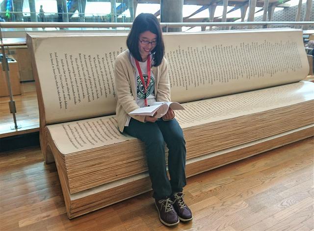 小澤彩果さんが本の形のベンチで読書している写真